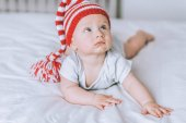 beautiful infant child in striped red and white hat with pompom looking up in bed