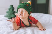 infant child in adorable knitted hat in shape of christmas tree playing with holiday decoration in bed