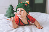 Fotografie infant child in adorable knitted hat in shape of christmas tree playing with holiday decoration in bed