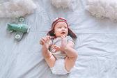 Blick von oben auf verträumtes Kleinkind mit Pilotenhut und Spielzeugflugzeug umgeben von Wolken aus Baumwolle im Bett