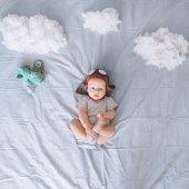 álmodozó gyermek gyermek kísérleti térdzokni játék síkon körül a felhők pamutból, az ágyban, felülnézet