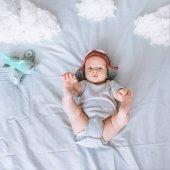pohled shora kojenecké dítěte v pilotní čepice s hračka letadlo s mraky z bavlny v posteli