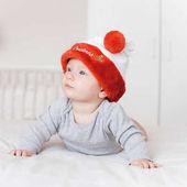 Fényképek santa kalap feküdt az ágyon, és keres el-imádnivaló csecsemő gyermek portréja