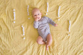 Fotografie top view of adorable infant surrounded with exclamation marks made of cotton balls in bed