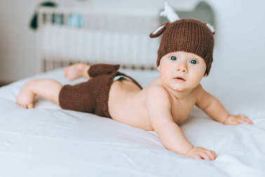 cute infant child in knitted deer costume in bed
