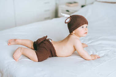 infant child in knitted deer costume lying on tummy in bed