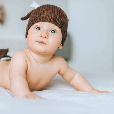 Close-up shot of beautiful infant child in knitted deer hat in bed stock vector
