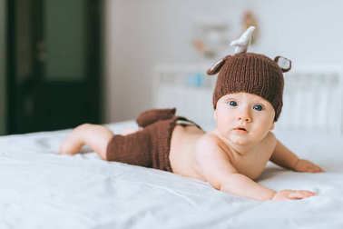 adorable infant child in knitted deer costume in bed