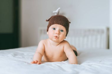 surprised emotional infant child in knitted deer hat in bed