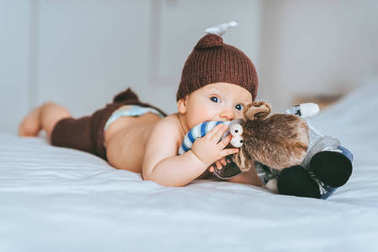 infant child in knitted deer costume playing with toy moose in bed