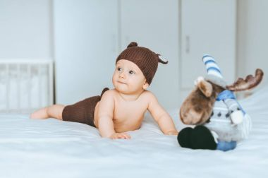 adorable infant child in knitted deer shorts and hat in bed with toy moose