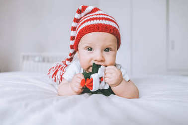 infant child in striped hat playing with toy christmas tree in bed