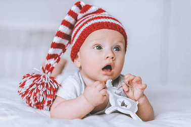 adorable infant child in striped red and white hat with toy deer in bed