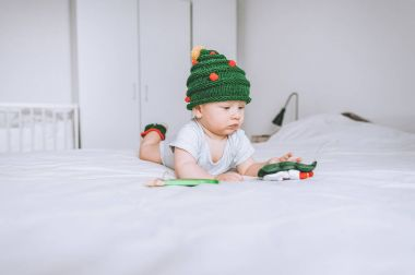 infant child in adorable christmas tree knitted hat in bed