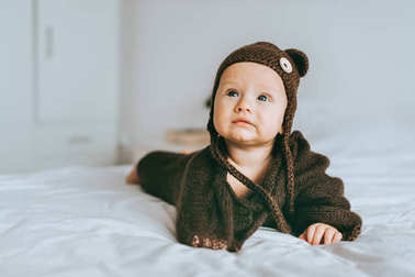 beautiful infant child in brown knitted hat and blanket in bed