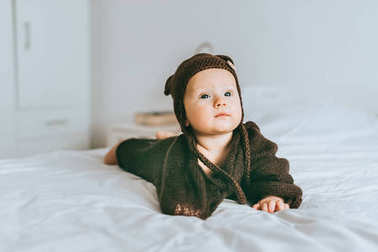 adorable infant child in brown knitted hat and blanket in bed