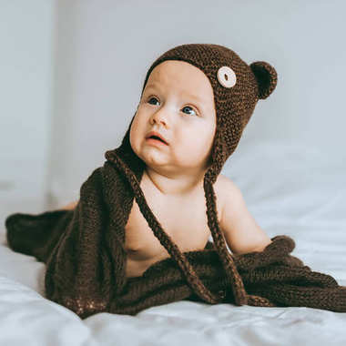 infant child in brown knitted hat with blanket in bed