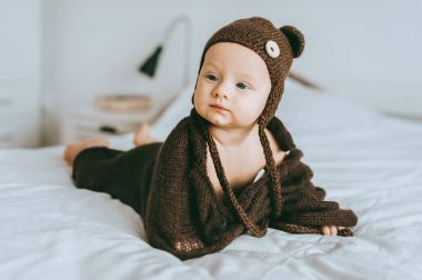 infant child in brown knitted hat and blanket in bed looking away