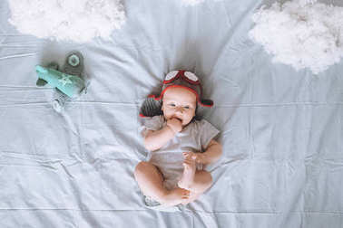 top view of adorable infant child in pilot hat with toy plane surrounded with clouds made of cotton in bed