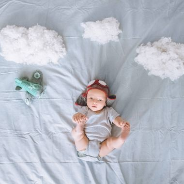 top view of adorable infant child in knitted pilot hat with toy plane surrounded with clouds made of cotton in bed