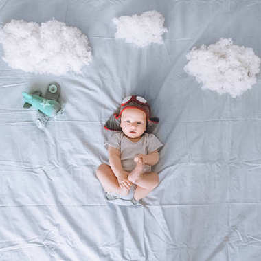 Top view of dreamy infant child in knitted pilot hat with toy plane surrounded with clouds made of cotton in bed stock vector