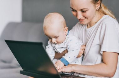 smiling mother holding little infant child and using laptop together