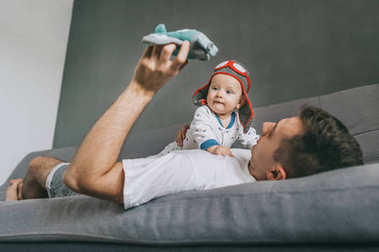 father holding toy plane and playing with adorable infant child wearing knitted pilot hat