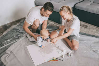 high angle view of happy young family with beautiful little infant child painting together on floor at home
