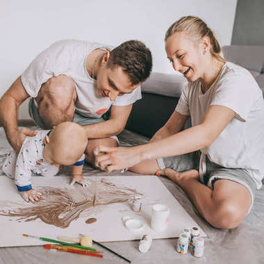 beautiful happy young family with cute little child painting together on floor at home
