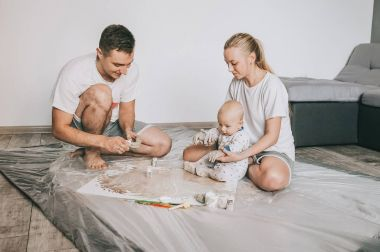 beautiful happy young family with infant child painting together on floor