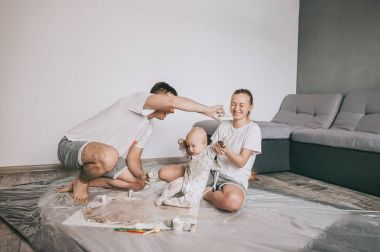 happy young family with cute infant child painting together on floor