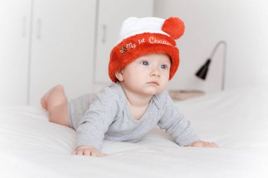portrait of beautiful little infant child in santa hat lying on bed