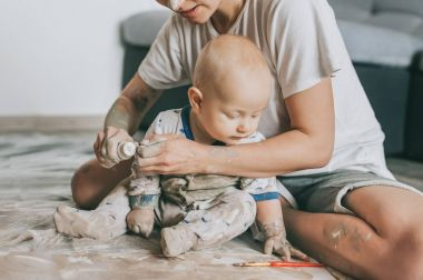 cropped shot of mother and infant child painting together on floor