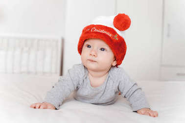 portrait of cute little infant child in santa hat lying on bed