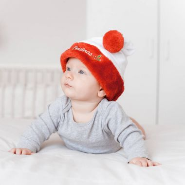 portrait of adorable infant child in santa hat lying on bed and looking away