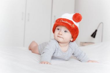 portrait of beautiful infant child in santa hat lying on bed and looking away