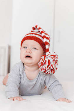 portrait of cute little infant child in knitted hat lying on bed