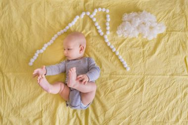 top view of adorable funny infant lying under house roof made of cotton balls and cotton cloud on bed