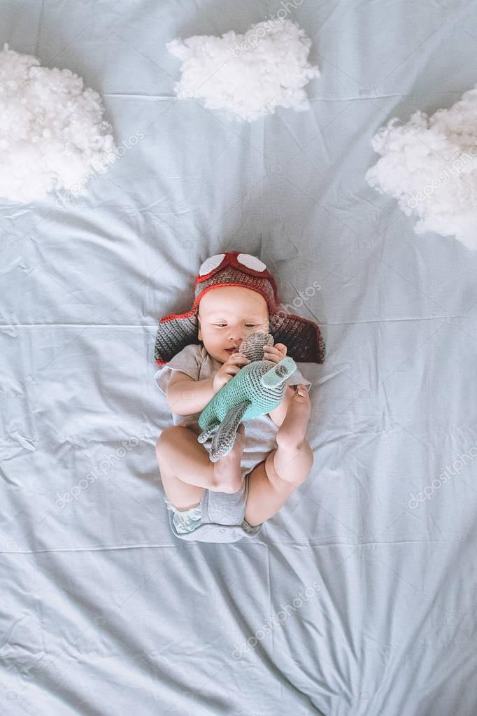 top view of beautiful infant child in pilot hat with toy plane surrounded with clouds made of cotton in bed