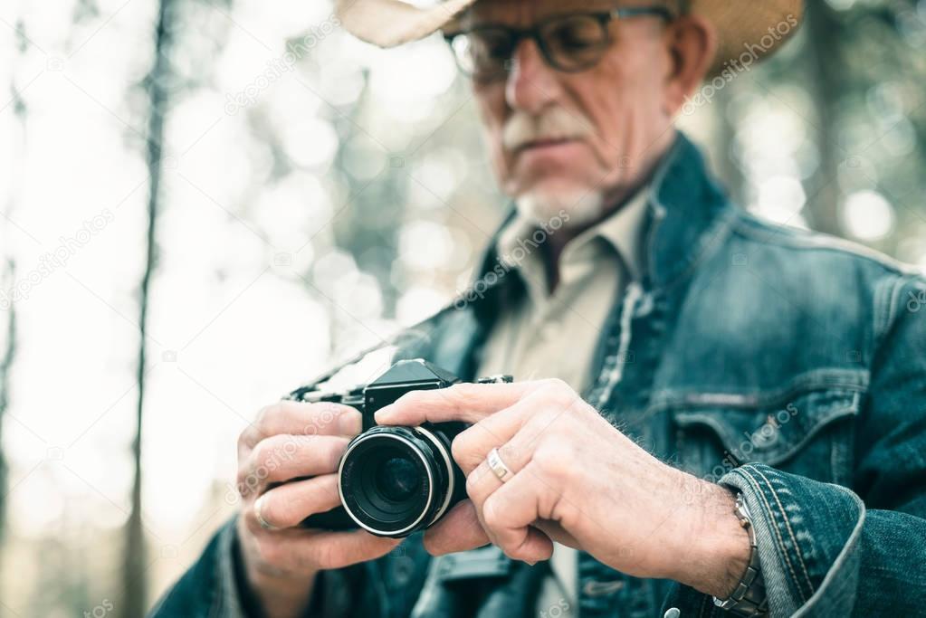 Senior photographer adjusting camera.