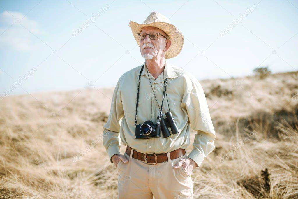 Senior safari man in field.