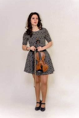 a girl in a dress is holding a violin
