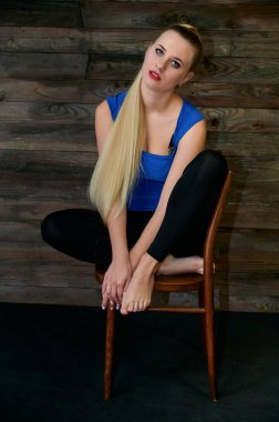 Art concept of a stylish model portrait. Portrait of a slender woman with long beautiful hair and excellent make-up on a creative background of wood in the loft style.