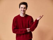 Portrait of a young Caucasian man with short hair and a white-toothed smile in a burgundy sweater on a pink background. Standing and talking right in front of the camera showing hands.