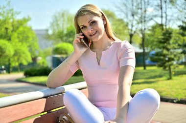 Photo of a cute caucasian girl uses a smartphone for an outdoor conference. Blonde model posing while sitting on a bench in sunny weather in a city park.