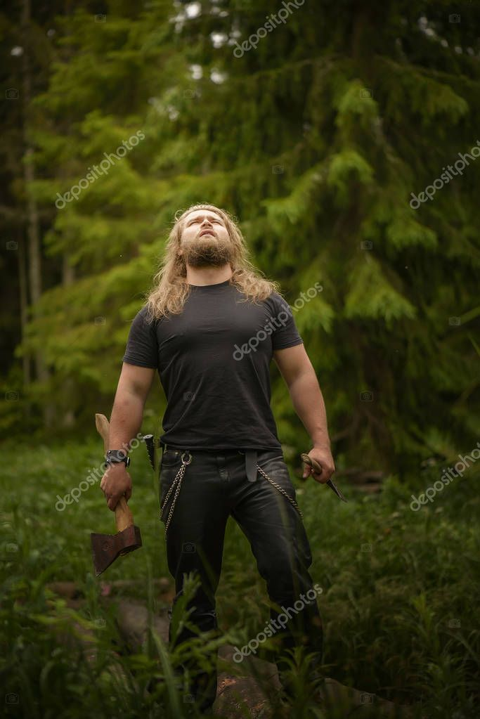 long hair Brutal man with axes in a forest