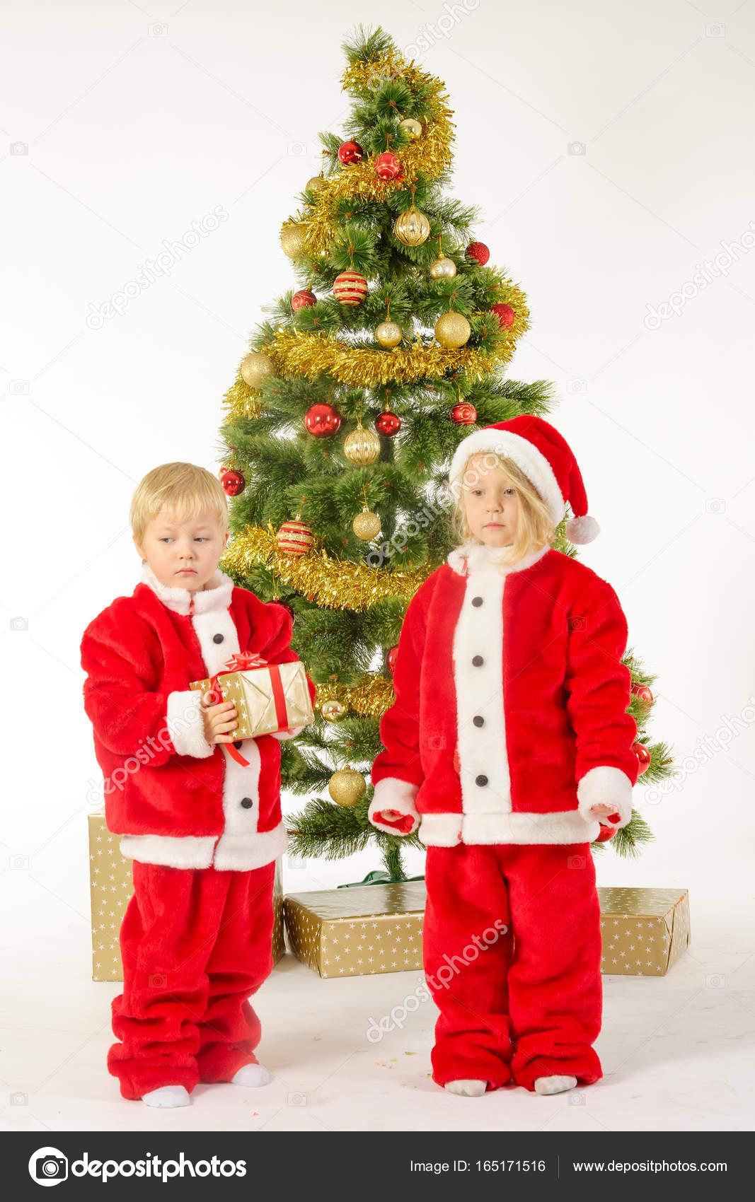Niedliche kleine Kinder teilen Weihnachtsgeschenke in der Nähe von ...