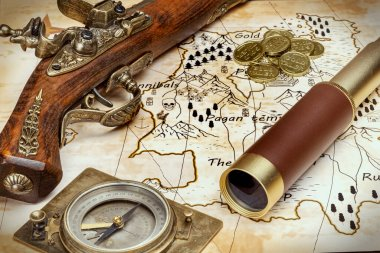 an old pistol, an old compass, a spyglass, and gold coins on a pirate treasure map