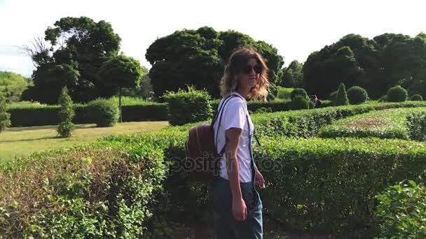 Lassú mozgás A lány a kerti labirintus kaland / gyönyörű lány sétál a labirintus kert. Csodálatos zöld természet.