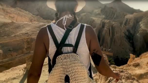Dívka chodí v oáze. Úžasný výhled na skalnaté hory / dobrodružství krásné dívky. Výlet do africké Oasis, úžasný výhled na skalnaté hory